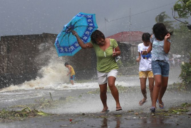Residents walk along the coastal village while strong winds from Typhoon Haiyan battered Bayog town in Los Banos, Laguna, south of Manila, on Friday