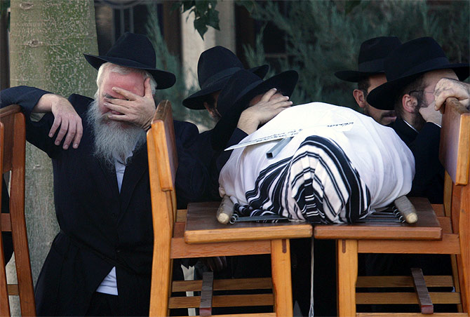 A mourner besides the body of Rabbi Gavriel Holtzberg during the funeral for him and his wife, Rivka, in Kfar Chabad near Tel Aviv. The Rabbi and wife were killed in the 26/11 terror attacks.