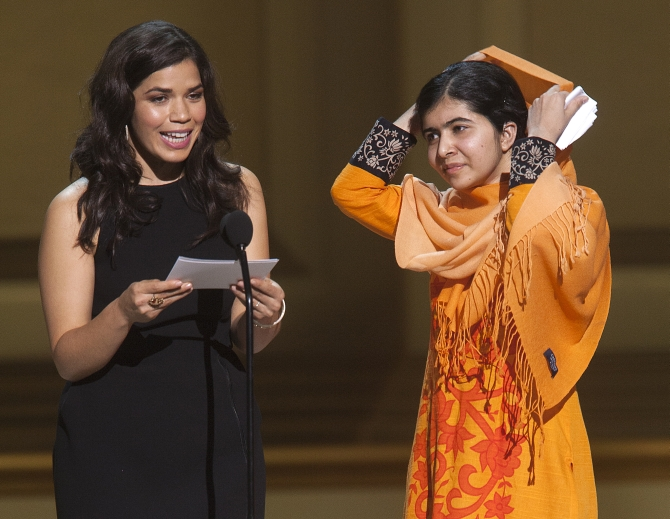 Actor America Ferrera speaks as Malala Yousafzai looks on after receiving her award during the Glamour Magazine Women of the Year event in New York