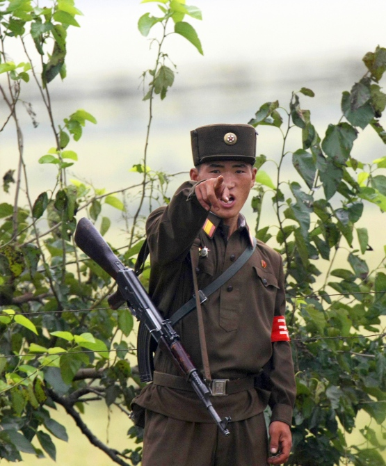 A North Korean soldier points at visitors near the North Korean town of Sinuiju, opposite the Chinese border city of Dandong.
