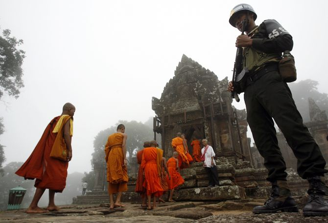 Monks walk past a Combodian soldier to attend a Buddhism ceremony praying for peace called Krong Pealy at Preah Vihear temple