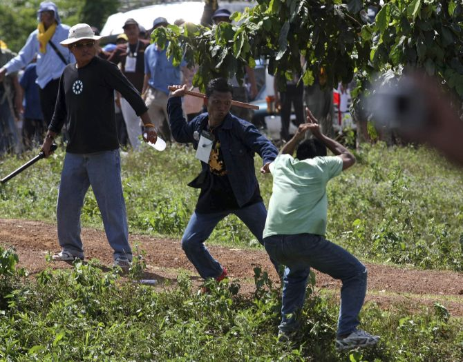 Supporters of the Thailand's People's Alliance for Democracy scuffle with a villager during a march along a highway leading to the Preah Vihear temple