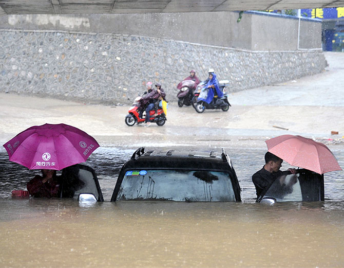People get out of a stranded car at a flooded underpass amid heavy rainfalls under the influence of Typhoon Haiyan, in Nanning, Guangxi Zhuang Autonomous Region