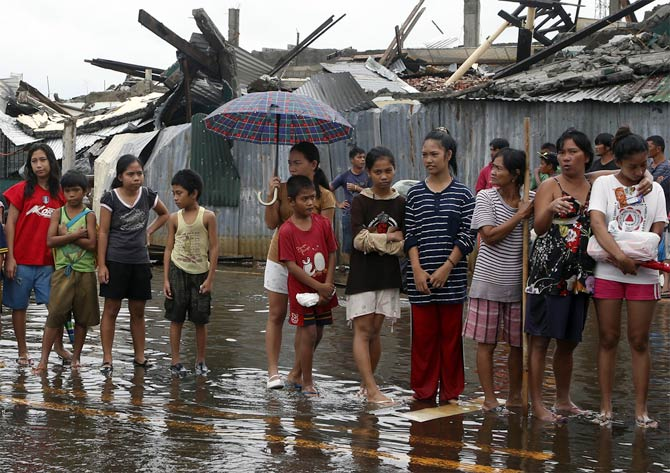 Typhoon victims queue up for free rice at Tacloban city, which was battered by Typhoon Haiyan, in central Philippines