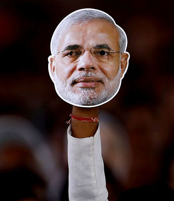 A man holds up a mask of Narendra Modi at a poll rally