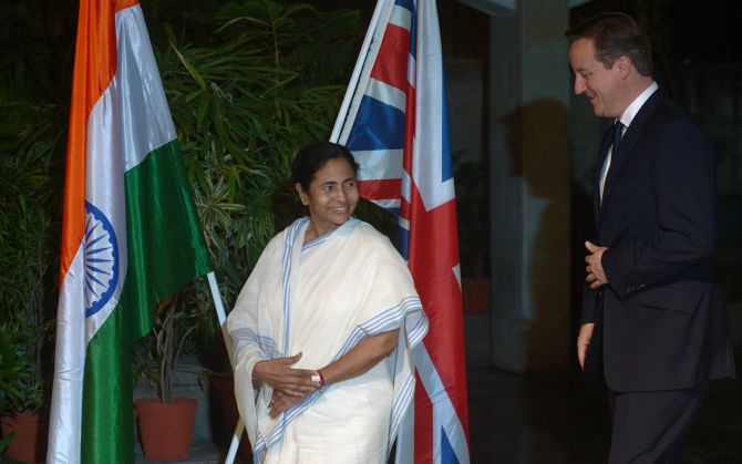 Britain's Prime Minister David Cameron walks with the Chief Minister of West Bengal Mamata Banerjee at the British Deputy High Commission in Kolkata