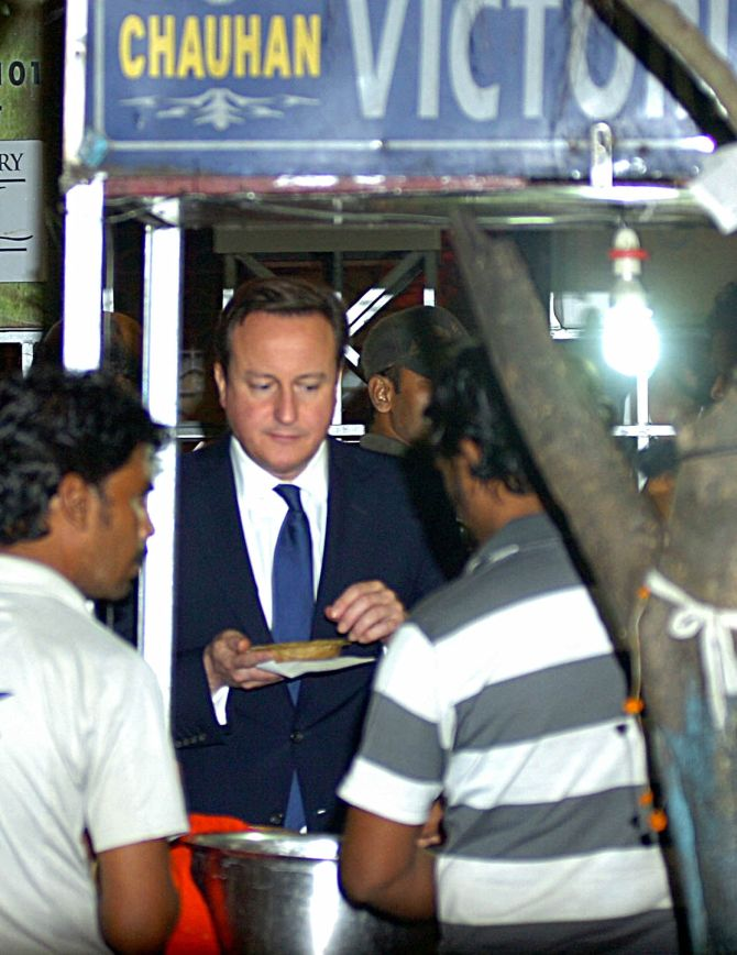 British Prime Minister David Cameron having 'dal bora' from a roadside shop during his Kolkata visit