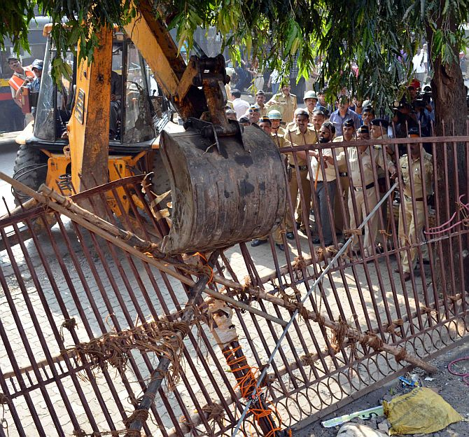 A bulldozer forces down the gate at the Campa Cola compound.
