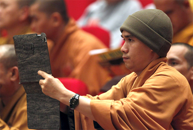 A monk films, with an iPad, a ceremony in Hanoi, Vietnam