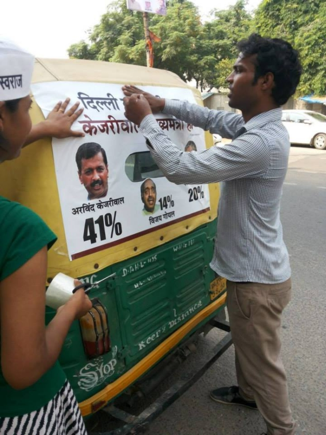 AAP supporters put up posters depicting results of poll surveys on an autorickshaw in Delhi