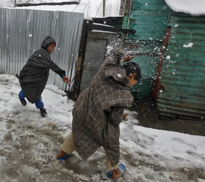 Kashmiri boys play in snow as temperatures drop in the Valley