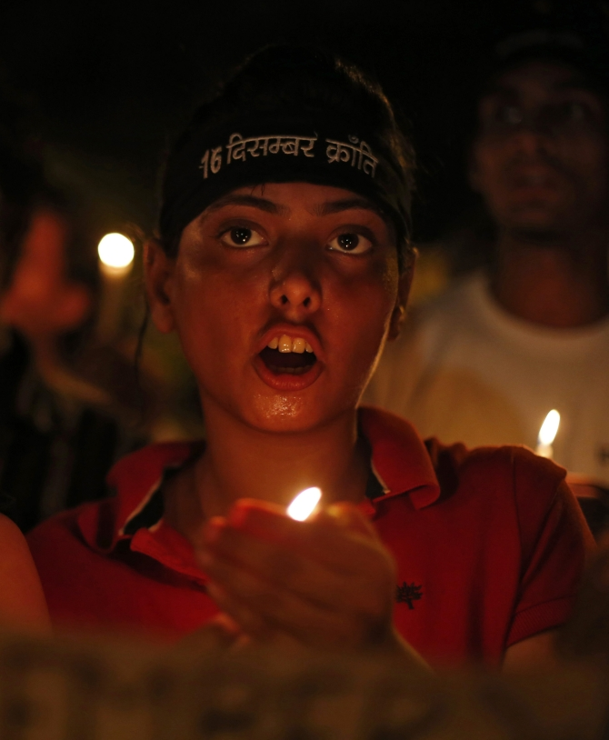 Demonstrators shout slogans as they hold candles during a candle light vigil for the Delhi gang rape victim