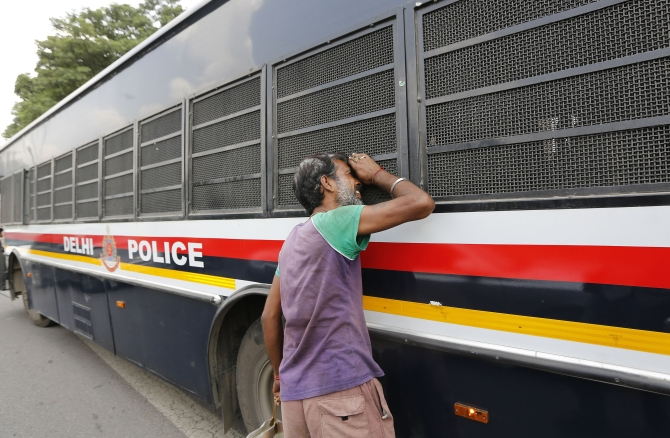 A man peeks into the police vehicle carrying four men who were sentenced to death for the fatal gang-rape