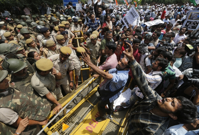 Demonstrators shout slogans as they try to cross a police barricade during a protest against the gang rape