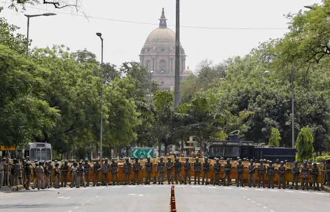 Policemen stand guard to stop protesters from marching towards Parliament