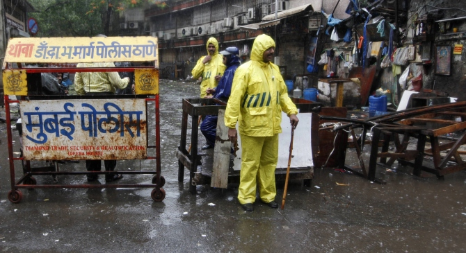 Policemen stand guard in the rain next to a barricade they installed at one of the sites of triple explosions in Mumbai on July 13, 2011, near the Opera House.