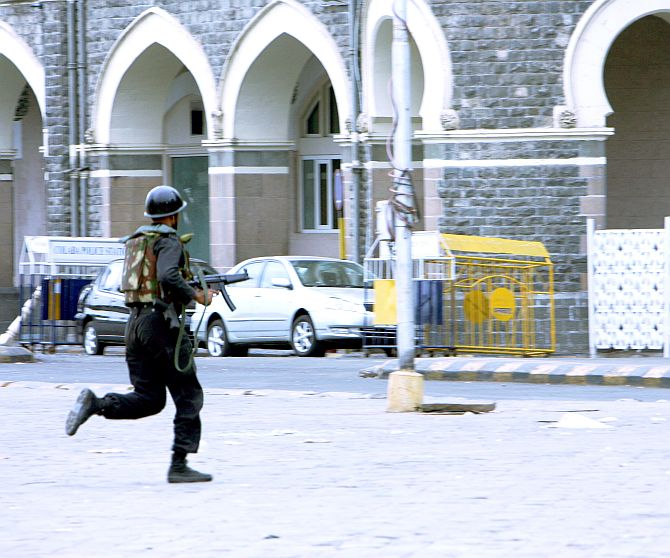 An NSG commando takes position outside the Taj hotel.