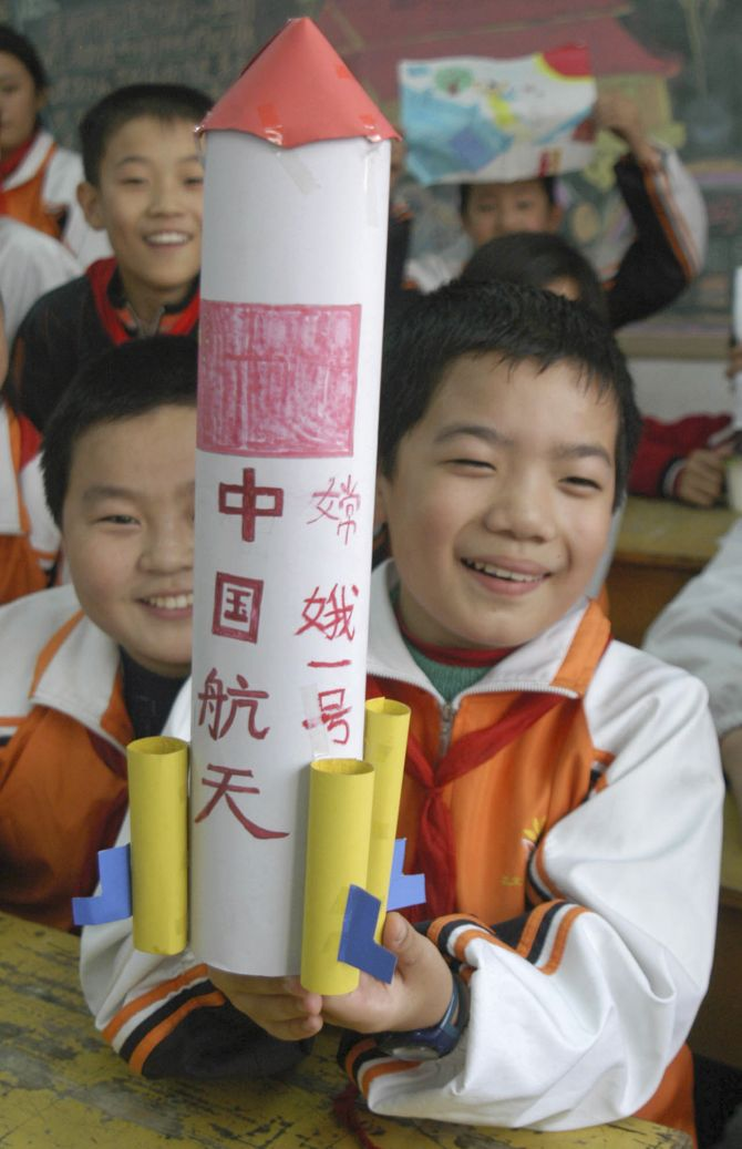 A pupil shows his handmade model of the Long March 3A carrier rocket in celebration of the successful launch of China's first lunar probe, Chang'e One, at a primary school in Huaibei, east China's Anhui province