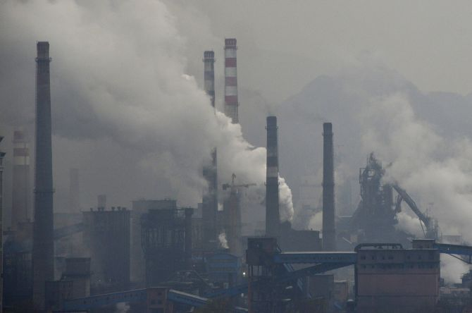 Smoke rises from chimneys and facilities of steel plants on a hazy day in Benxi, Liaoning province, China. A chronic shortage of natural gas is hurting China's plan to move away from burning coal to heat homes and offices, raising the prospect of more choking air pollution.