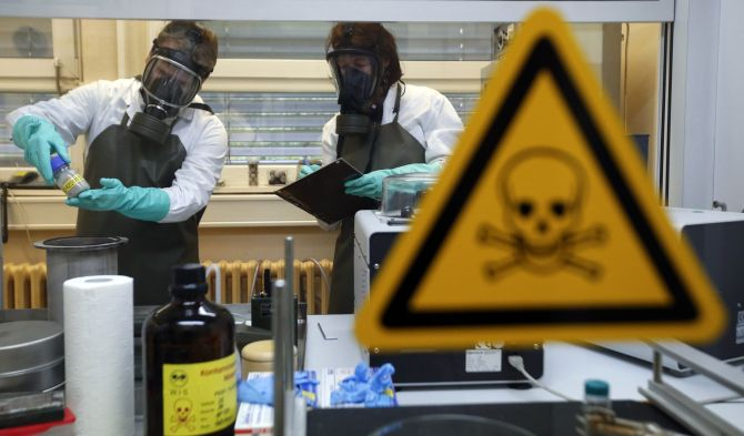 Employees of the Research Institute for Protective Technologies, Nuclear, Biological and Chemical Protection inspect a dummy sample which is contaminated with a substance similar to the chemical weapon Sarin, during a demonstration in Munster.