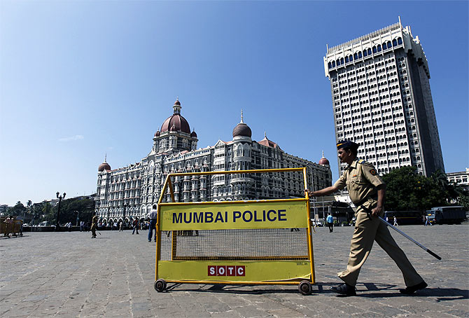 A policeman pushes a barricade in front of Taj Mahal Hotel