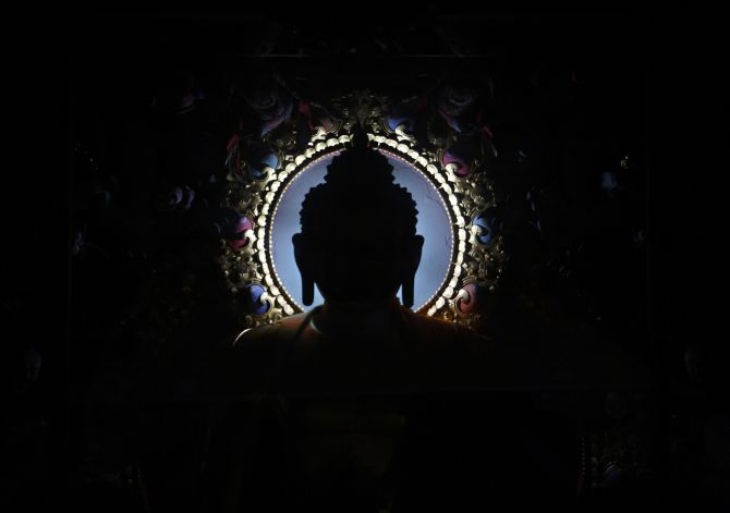 An idol of Buddha is silhouetted at the Tibetan Monastery in Lumbini, south-west of Kat