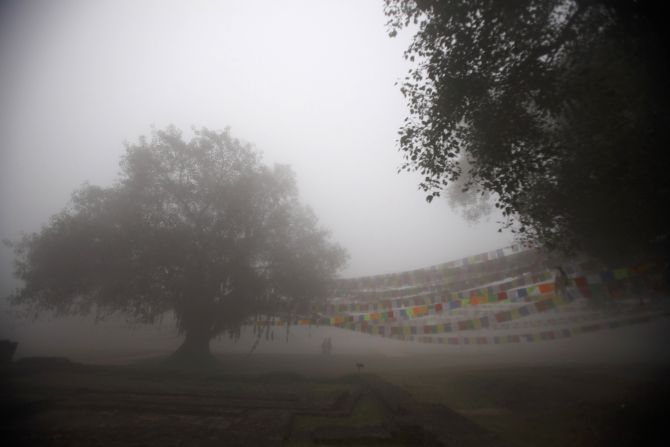 People walk past prayer flags on a foggy morning at the Maya Devi Temple in Lumbini