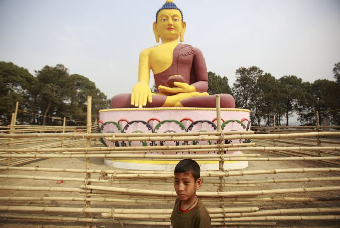 A child plays in front of a giant idol of Lord Buddha in Lalitpur