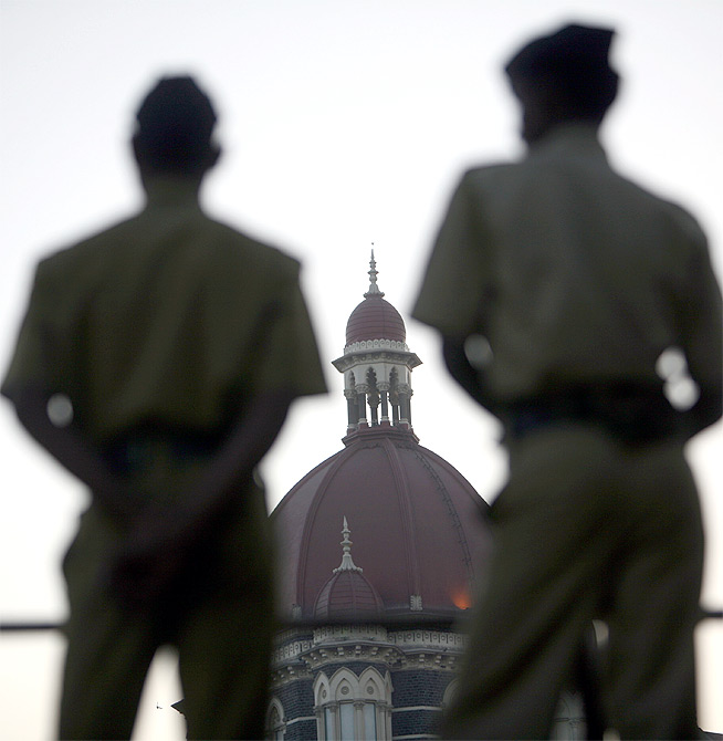 Policemen stand guard outside the Taj Mahal hotel.