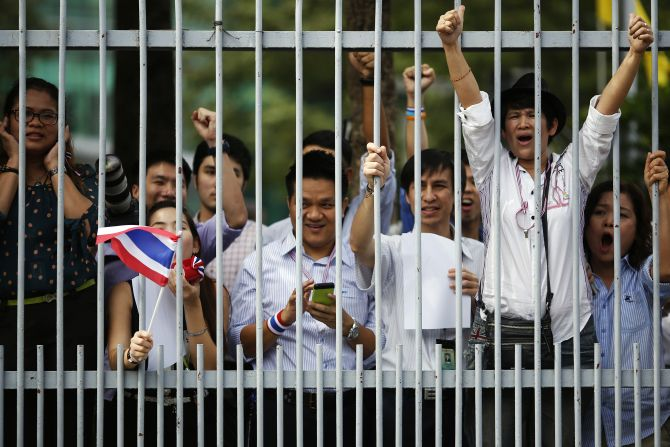 Office workers react as anti-government protesters march past their building in Bangkok