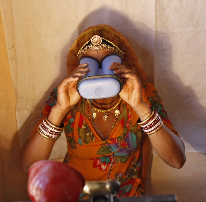 A villager goes through the process of eye scanning at Merta district in Rajasthan
