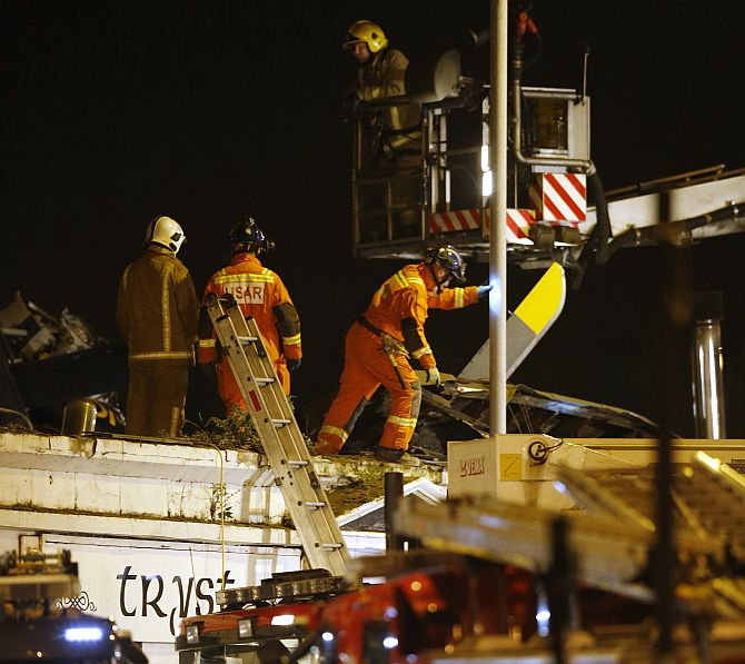 Rescue workers examine the wreckage of a police helicopter which crashed onto the roof of the Clutha Vaults pub in Glasgow, Scotland