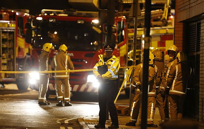 Rescue workers gather near the scene where a police helicopter crashed onto the roof of the Clutha Vaults pub in Glasgow