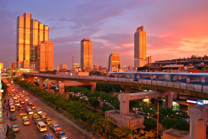 A spectacular sunset in Bangkok, showing the skytrain and modern skyline down Thanon Naradhiwas Rajanagarindra.