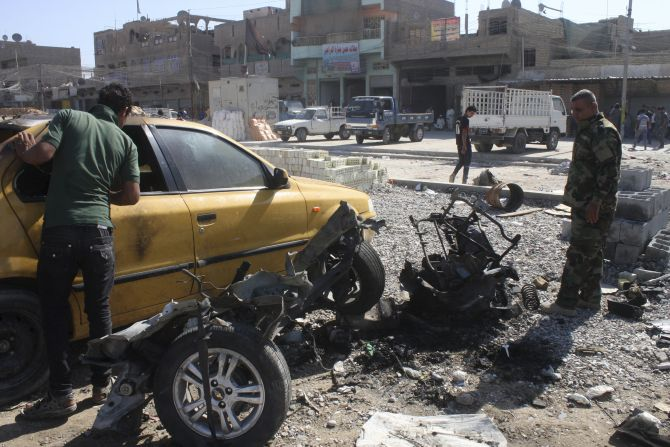 A policeman examines the remains of a vehicle that was used as a car bomb in Baghdad's Sadr City