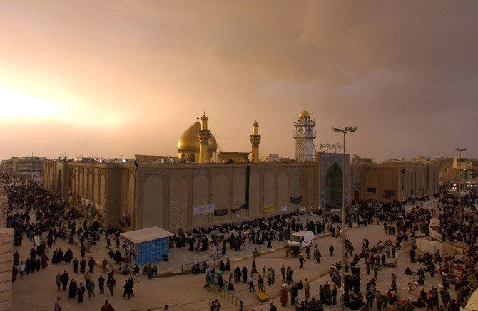 Iraqis walk past the shrine of Imam Ali in Najaf at sunset before a dust storm in Najaf