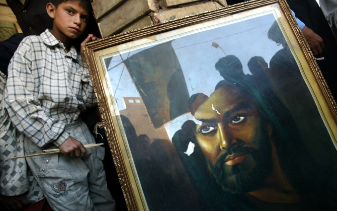Shiite Muslims are reflected in a portrait of Imam Hussein, the son of Imam Ali outside the shrine of Imam Ali to mark the anniversary of the death of Mohammed in Najaf