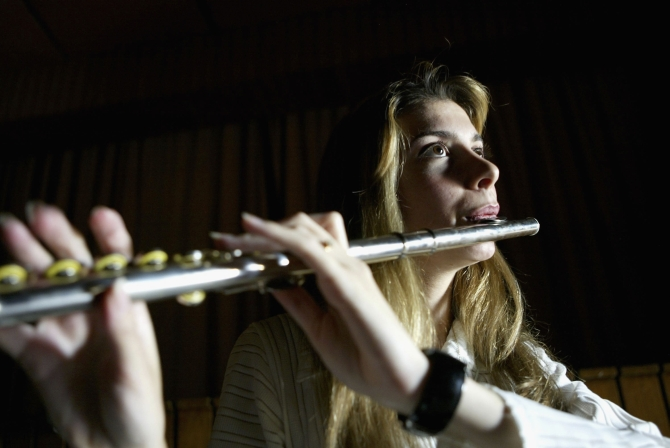 A member of 'Ishtar' plays the flute during a practice session on in Baghdad