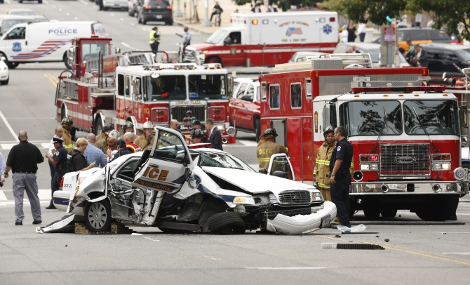 Rescue personnel stand around a smashed US Capitol Police car followin