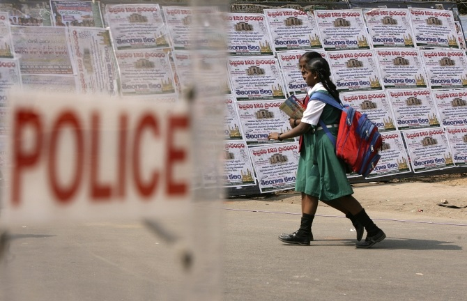 Schoolgirls walk past a police barricade in Hyderabad