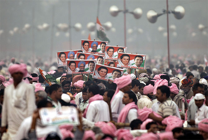 Supporters of Congress party hold posters of Prime Minister Manmohan Singh, Congress President Sonia Gandhi and Rahul Gandhi