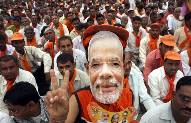 A supporter wears a mask of Narendra Modi during a rally in Gujarat