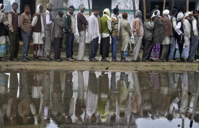 Voters stand in a queue as they wait for their turn to cast their ballot at a polling station in Shravasti town in Uttar Pradesh