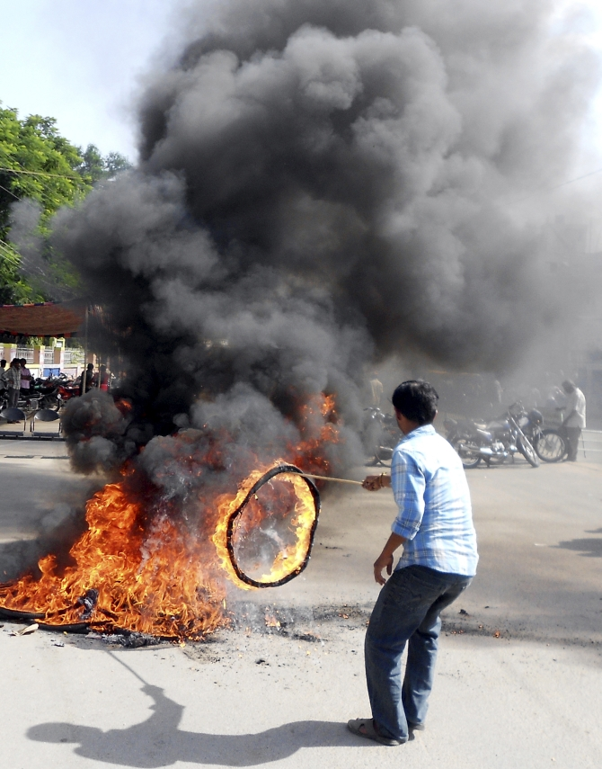 A protester burns a tyre during a protest against the creation of Telangana state, in Ananthapuram district in the southern Andhra Pradesh