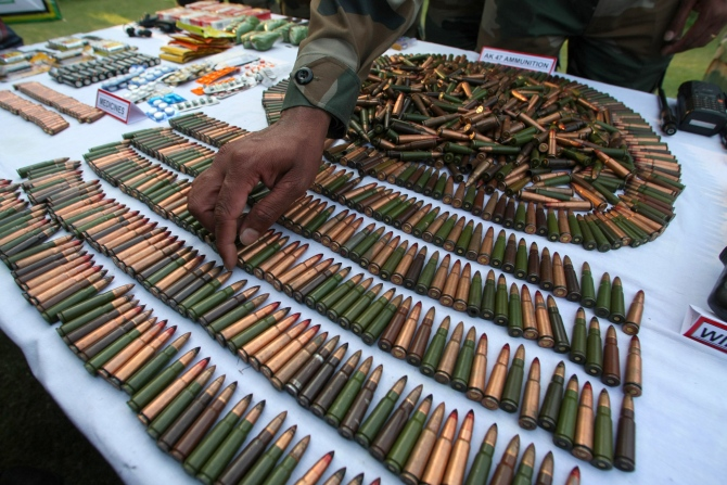 An army officer gestures at the arms and ammunition recovered during the Keran operation