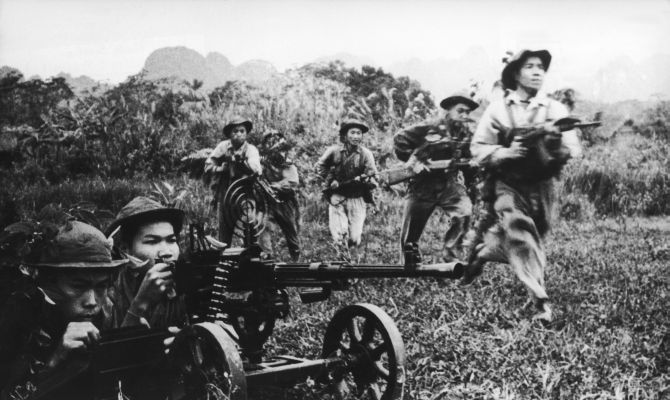 Viet Cong soldiers move forward under covering fire from a heavy machine gun during the Vietnam War in 1968.