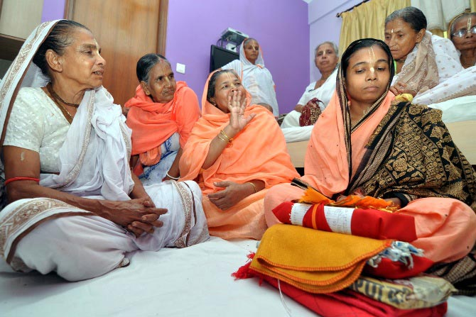 Kunjaleena Dasi (in saffron) and her adopted daughter, Basana Dasi (in saffron and black) with other ashramites.