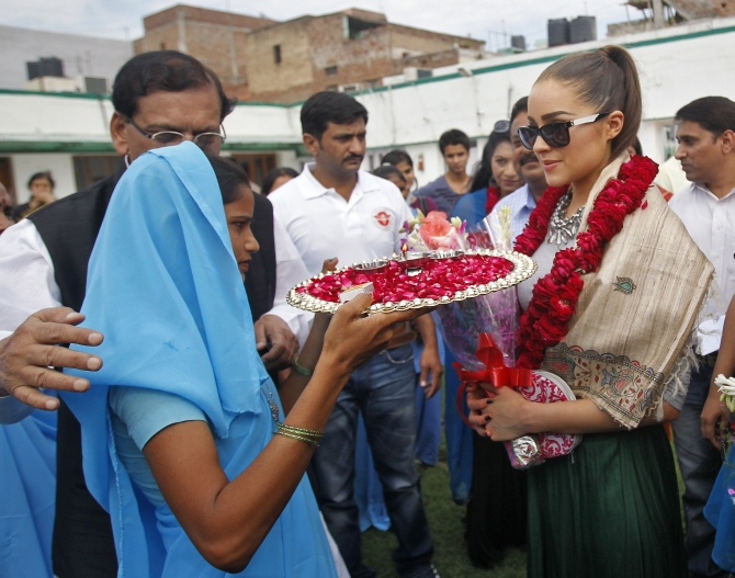 Miss Universe 2012 and Miss USA 2012 Olivia Culpo (R) wearing floral garlands, gets a traditional Indian welcome upon her arrival at a school in New Delhi on Sep