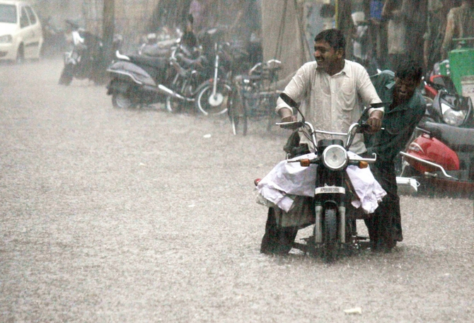 A motorist struggles as he wades his way through a water-logged street in Hyderabad