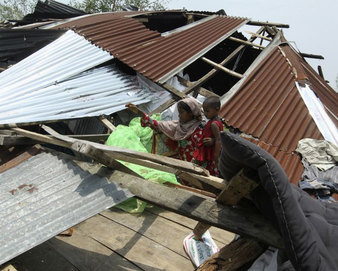 A woman tries to retrieve her belongings after her house was destroyed by cyclone Mahasen, in Kuakata, Bangaladesh in May, 2013.